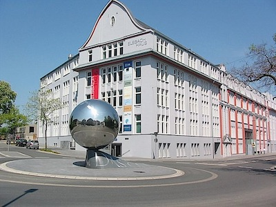 Luciano Fabros artwork La Palla (the ball) reflects its surroundings in front of the Elsbachhaus. The poem Der Ball (the ball) by Rainer Maria Rilke is written between two traffic lanes on a length of 153 meters
